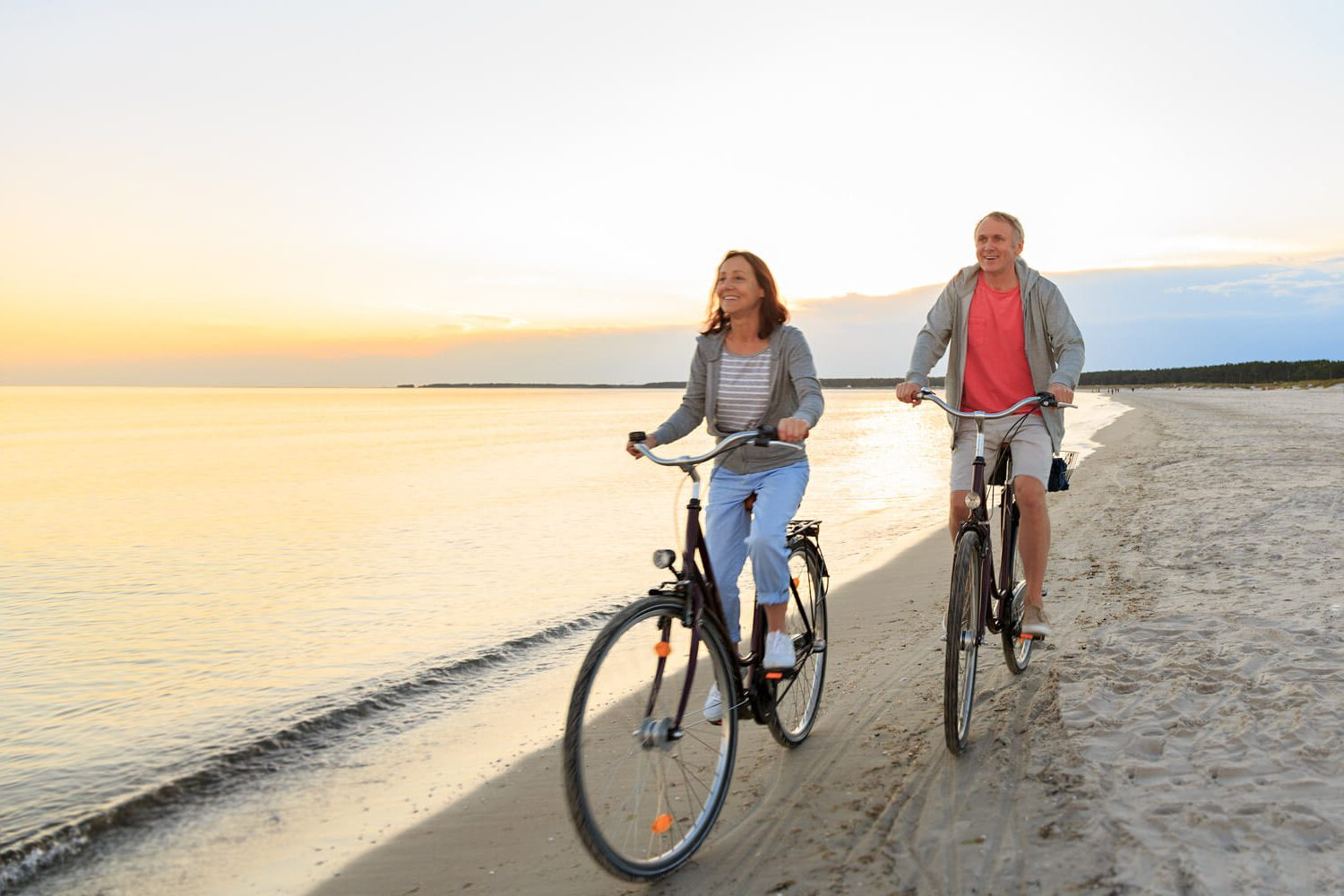 senior-couple-cycling-beach